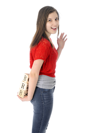 A happy young teen waving good-bye as she holds alphabet blocks showing the letters BRB (be right back).  On a white background.