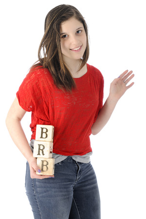 A pretty young teen happily waving as she hold rustic alphabet blocks with the letters she uses on her phone:  BRB, standing for be right back. photo