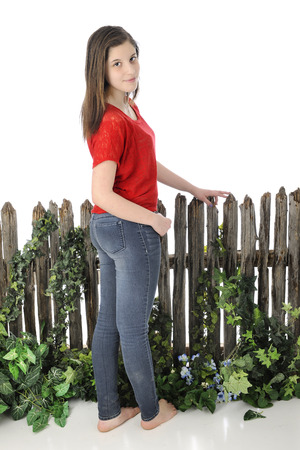 A beautiful young barefoot teen standing before an old vine-covered fence.  Shes looking back at the viewer. On a white background.