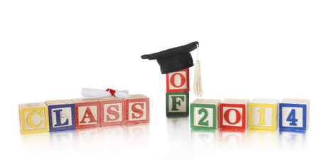 A childs colorful alphabet blocks arranged to say Class of 2014.  Theyre topped with a tiny diploma and black cap with a white tassel.  On a white background. photo