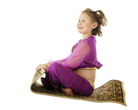 A young elementary 'genie' delightedly flying through the air on her flying carpet.  On a white background. photo