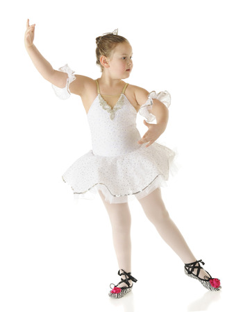poised: A young elementary ballerina poised to being her perfomrance in her white dance costume.  On a white background. Stock Photo