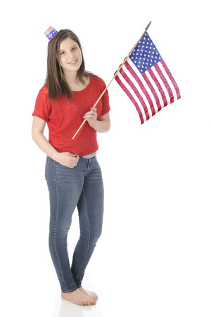 A pretty, barefoot young teen carrying an American flag while wearing a tiny Uncle Sam hat.  On a white background. photo