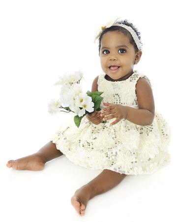 Een mooi bby meisje, blootsvoets en gekleed, gelukkig bezit van een klein boeket van witte bloemen. Op een witte achtergrond. Stockfoto