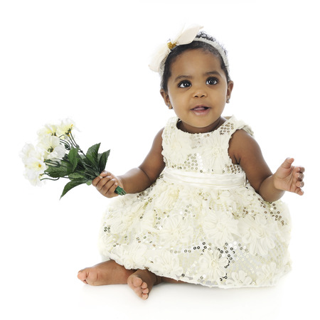 A beautiful baby girl looking up for approval in her white hair bow and sequin dress.  She holds a small bouquet of white flowers.  On a white background.
