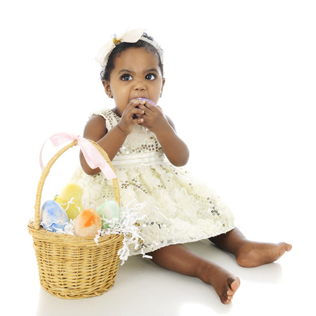 A beautiful, dressed up baby girl, and Easter basket by her side.  Shes making a face as she tries to bite one of the Easter eggs.  On a white background. photo