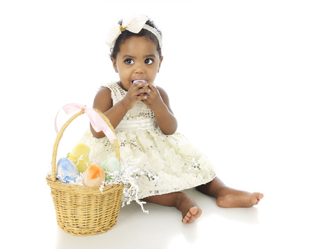 An adorable baby girl all dressed up with an Easter basket by her side.  Shes attempting to eat one of the colored eggs.  On a white background,