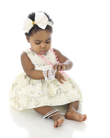 A beautiful baby girl all dressed up, examining the bracelet of beads she wears on her wrist.  On a white background. photo