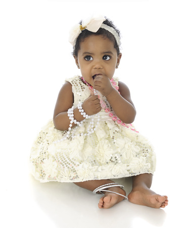 An adorable baby girl, dressed up in a white hair bow, dress and jewelery.  She's tasting the pink necklace that she wears.  On a white background. photo