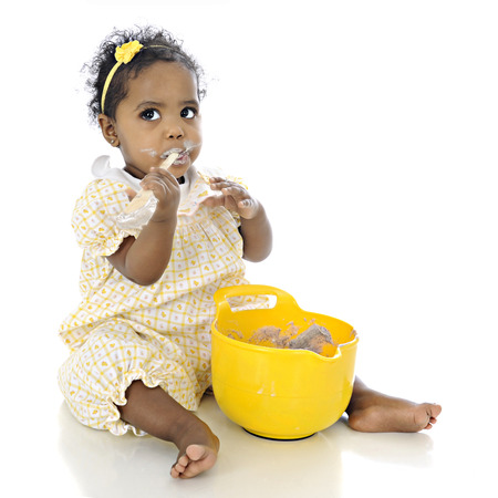 An adorable baby girl looking up questioningly while eating pudding from a mixing bowl before her.