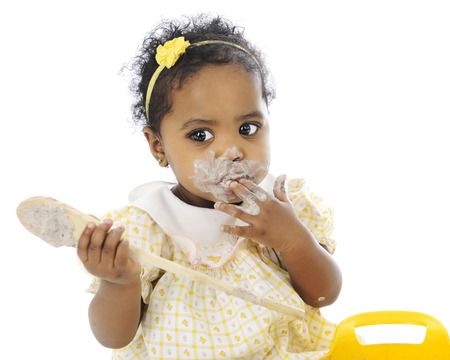 mess: Close-up of an adorable baby girl sitting with a wooden spoon in her hand and a pudding-mess around her mouth.  Stock Photo