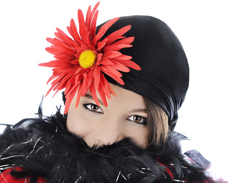 boas: Close-up of  beautiful teen flapper in a black hat with a large red flower.  Her face is hunkered down into the boas up ther her nose.