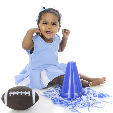 An adorable baby cheerleader  looking distressed in her uniform and surrounded by a football, pompoms and megaphone.  On a white background. Stock Photo