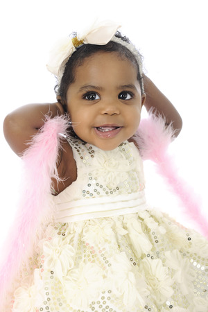 A beautiful baby girl happily showing off in her white hair bow, sequin dress and pink boa.  On a white background.