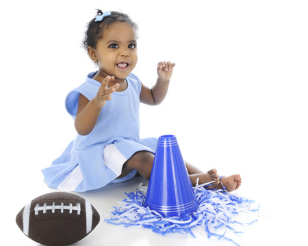 black cheerleader: An adorable baby cheerleader  in a blue uniform and with a football, pompoms and megaphone.  On a white background.