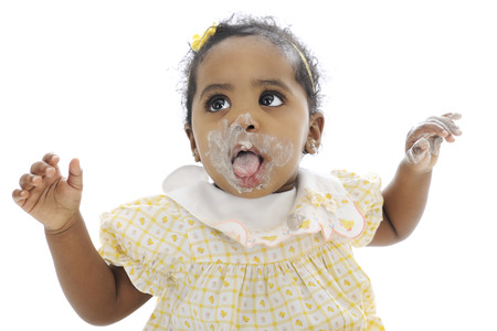 smeared hand: Close-up of an adorable baby girl looking up, with her messy mouth wide opened and hand up wanting help to get cleaned up.  On a white background.