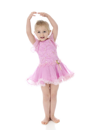 A beautiful preschool dancer showing the viewer her version of ballets first position.  On a white background. photo