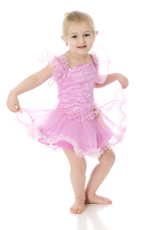 An adorable preschool dancer, curtsying in her ballerina costume.  On a white background. photo