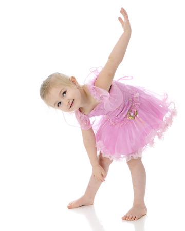 An adorable preschooler making up a dance move while in her ballet costume.  On a white background.