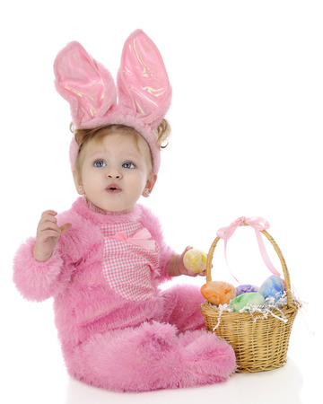 An adorable baby girl Easter bunny attempting to whistle as she sits by her basket filled with colorful eggs.  On a white background. photo
