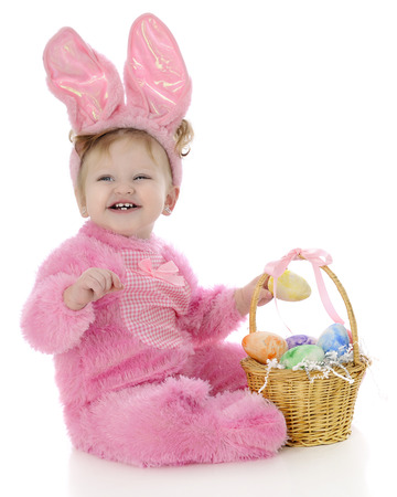An adorable baby Easter bunny laughing as she puts a colored egg in her Easter basket.  On a white background. photo