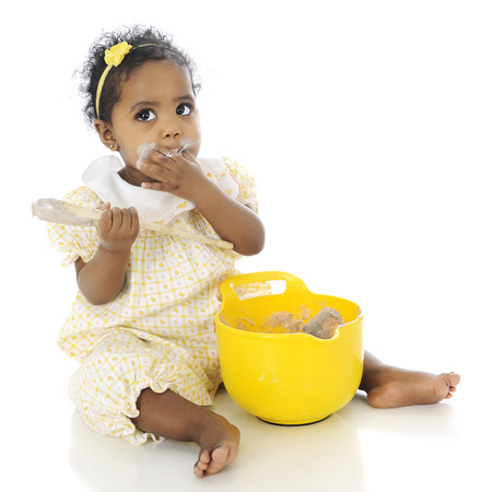 An adorable baby girl looking up as if innocent, while putting her hand over her mouth covered in pudding she's taking from the mixing bowl before her.  On a white background. Stock Photo - 27304330