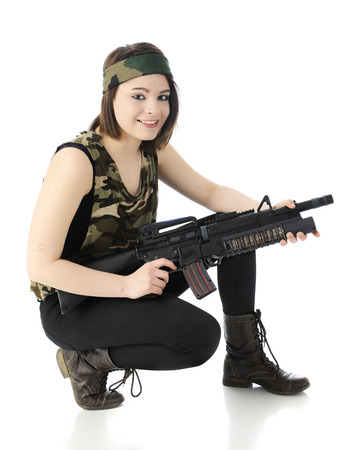 A beautiful teen gilr wearing comouflage and combat boots, happily squatting and poised with her machine gun   On a white background  photo