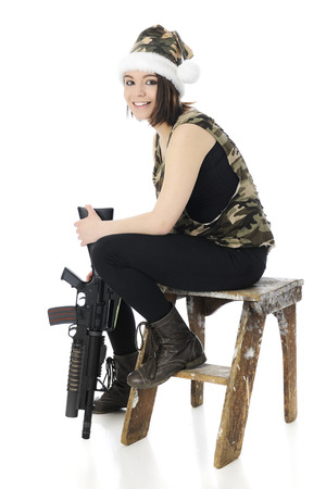 A beautiful teen girl happily sitting on a rustic wooden stool while propping a machine gun on the floor   She photo