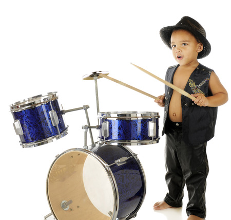 An adorable, barefoot preschooler dressed as a rock star, beating on a drum set.  On a white background.  Motion blur on the drum sticks.