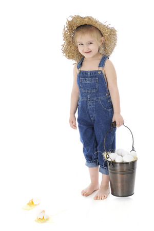 An adorable preschooler in rolled up overalls carrying a bucket of eggs.  Two broken ones lay by her bare feet.  On a white background. photo
