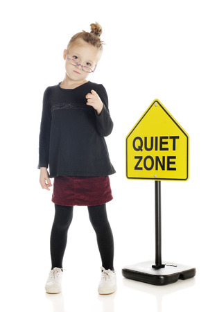 sternly: An adorable elementary teacherlibrarian sternly pinting her finger at the viewer in front of a quiet zone sign.  On a white background.