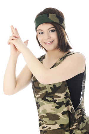 upraised: A beautiful teen girl happily looking at the viewer as she forms a gun with upraised hands.  On a white background.