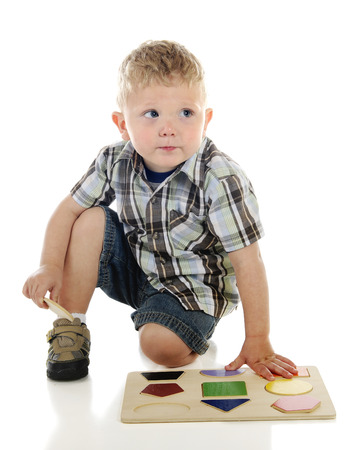 A young preschooler looking up for approval as he finishes his puzzle of shapes.  On a white background.