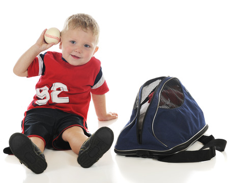 duffle: A young preschooler ready to toss the baseball hes just pulled from his sports bag.  On a white background.