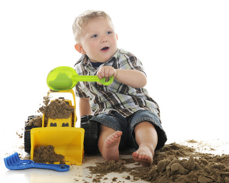 dumps: An adorable, young preschooler happily looking up as he dumps sand onto his toy bulldozer.  On a white background.