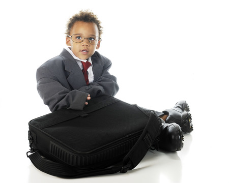computer case: An adorable tot sitting with his computer case while dressed in an oversized business suit and dress shoes   On a white background