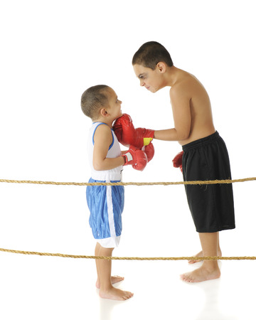 bare feet boys: A tough-acting elementary boxer with a shiner threatening his preschool brother while standing behind boxing ring ropes   On a white background