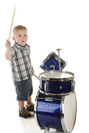 cymbol: A high view of an adorable preschool drummer.  Motion blur on upper drumstick.  On a white background.
