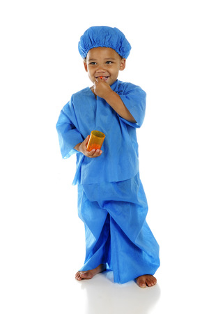 An adorable preschool doctor in blue scrubs, happily taking a pill from the pill bottle he holds.  On a white background. photo