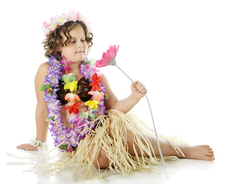 leis: An elementary hula dancer sitting mermaid-style in her grass skirt, coconut bra and flower leis, admiring a giant pink flower.  On a white background.