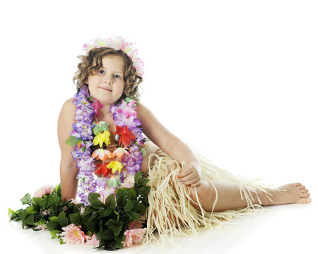 leis: An elementary hula dancer in flower leis and a grass skirt, relaxed among green foliage and pink flowers.  On a white background. Stock Photo