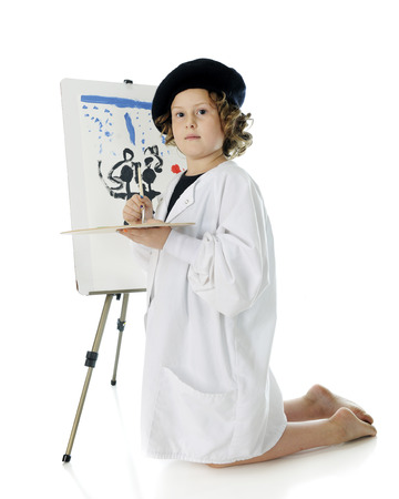 smock: A serious elementary girl kneeling as she paints on an easel in her French beret and white smock.  On a white background.