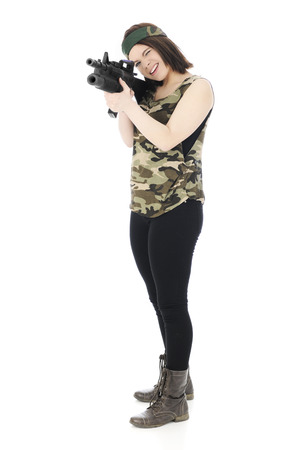 A beautiful teen in a camouflage headband and shirt, taking aim with a machine gun   On a white background  photo