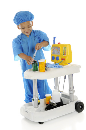 An adorable preschool  doctor  in blue scrubs happily drawing up an injection by his emergency cart   On a white background  photo