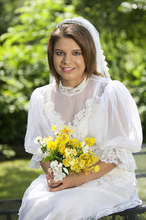 Close-up of a happy, beautiful young bride among summer foliage