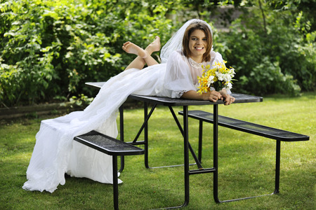 A beautiful young bride happily sprawled across a picnic table, barefoot in her wedding gown