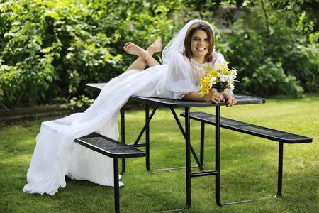 sprawled: Una joven y bella novia feliz tendido sobre una mesa de picnic, descalzo en su vestido de novia Foto de archivo