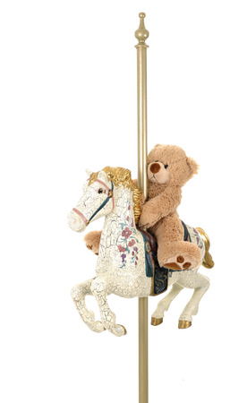 antiqued: A toy bear riding on an antiqued carousel horse.  Isolated on white.