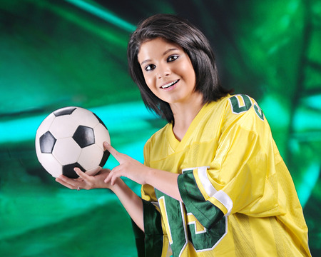 oversized: A pretty teen girl delightedly wearing an oversized yellow and green jersey while poised to toss a soccer ball.