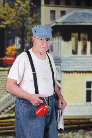 A senior train engineer outside the station house with his oil can and wiping rag.   Stockfoto